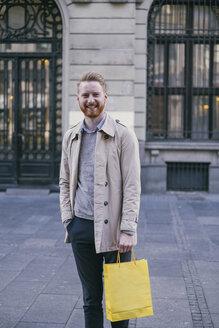 Portrait of smiling man holding shopping bag - MOMF00159