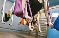 Group of women having a class of aerial yoga - MGOF03241