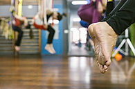 Feet of a woman in aerial yoga class - MGOF03244