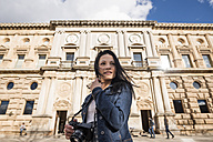 Spain, Granada, smiling young woman with camera at Albayzin - JAS01664