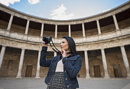 Spain, Granada, young woman taking pictures at the Alhambra - JAS01667