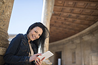 Spain, Granada, happy young woman with tablet at the Alhambra - JAS01673