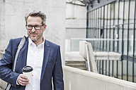 Portrait of businessman with coffee to go - FMKF03883