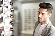 Young man looking for glasses at the optician's - JASF01681