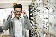 young man trying on glasses at the optician's - JASF01687
