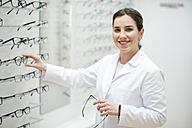 Female optician arranging glasses frames in her shop - JASF01696