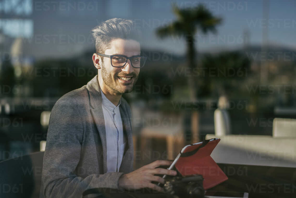 Young man sitting in bar, working with digital tablet - JASF01699 - Jaen Stock/Westend61