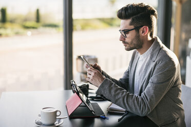 Young man sitting in bar, working with digital tablet and smartphone - JASF01702