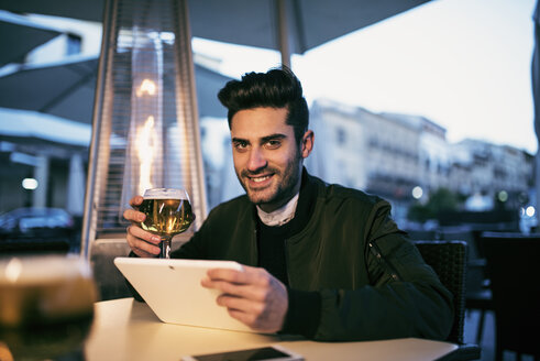 Young man drinking beer in a bar and uses his digital tablet - JASF01720