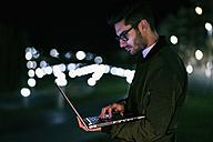 Young man using laptop at night - JASF01723