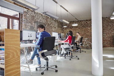 Group of people working in creative office, looking content - RHF01850