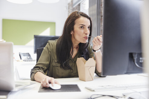 Businesswoman sitting in office, eating lunch - RHF01892