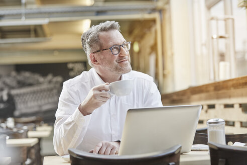 Smiling mature businessman in cafe with cup of coffee and laptop - FMKF03913