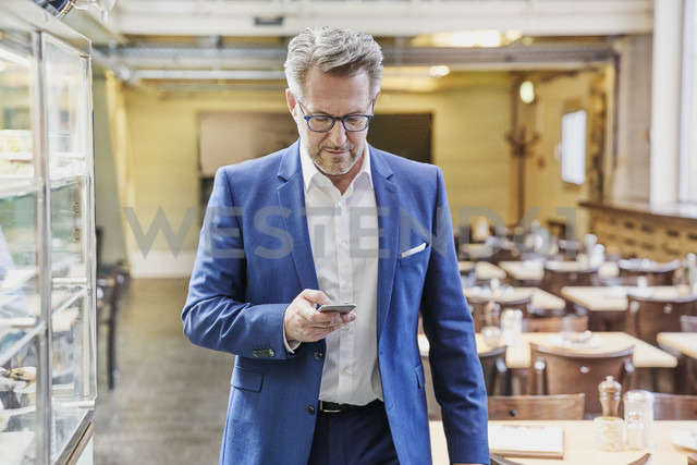 Mature businessman in cafe looking on cell phone - FMKF03931 - Jo Kirchherr/Westend61