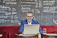 Portrait of confident mature businessman in cafe using laptop - FMKF03952