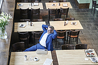 Mature businessman in cafe with laptop, cell phone and earbuds - FMKF03955