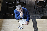 Mature businessman in cafe writing in diary - FMKF03958
