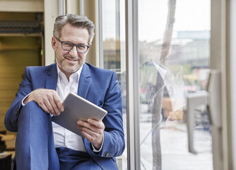 Smiling mature businessman using tablet at the window - FMKF03961