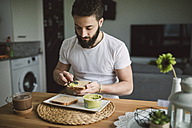 Young man having breakfast at home, toast with avocado cream - RAEF01836