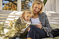 Mother with daughter on bench using tablet - KDF00723
