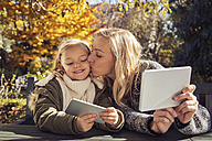 Mother with daughter at garden table holding tablet and cell phone - KDF00726