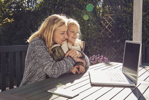Mother with daughter at garden table looking at laptop - KDF00729