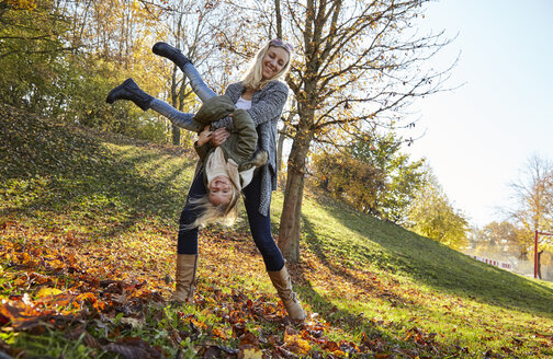 Mother and daughter playing in park in autumn - KDF00732