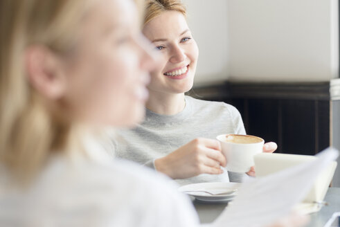 Smiling woman with colleague in a cafe - FMOF00206