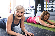 Two fit senior women having fun in gym - HAPF01455