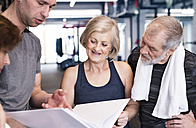 Group of fit seniors and personal trainer in gym looking in folder - HAPF01467