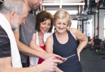 Group of fit seniors and personal trainer in gym looking at tablet - HAPF01470
