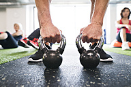 Close-up of man exercising with kettlebells in gym - HAPF01473