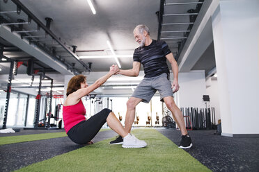 Senior man supporting wife in gym - HAPF01476