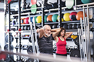 Senior mand and woman in gym exercising with medicine balls - HAPF01479