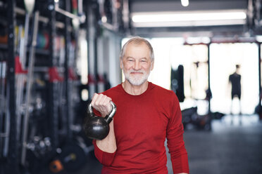 Senior man exercising with kettlebell in gym - HAPF01482