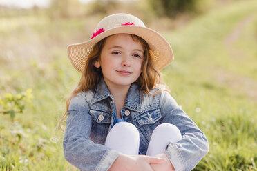 Portrait of girl wearing straw hat sitting on a meadow - NMSF00048