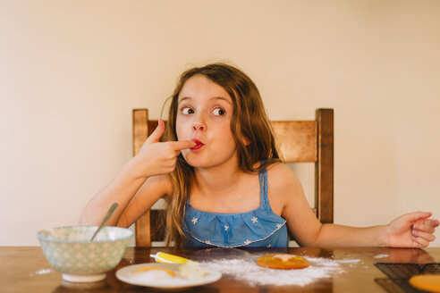 Portrait of girl decorating biscuits at home - NMSF00054