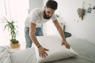 Young man making the bed at home - RAEF01844
