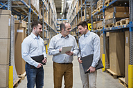 Three men with tablet talking in factory warehouse - DIGF01718