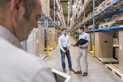 Two men with folder talking in factory warehouse - DIGF01730