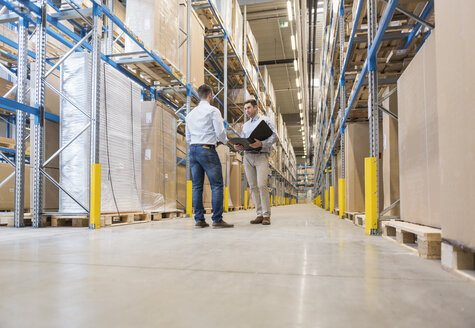 Two men with folder talking in factory warehouse - DIGF01733