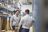 Two men talking in factory warehouse - DIGF01736