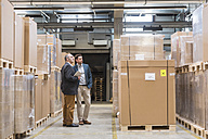Two men standing in factory warehouse - DIGF01751