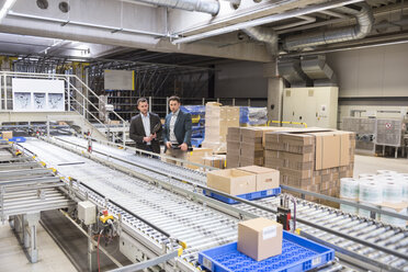 Two businessmen at conveyor belt in factory - DIGF01757
