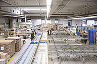 Three businessmen at conveyor belt in factory - DIGF01760