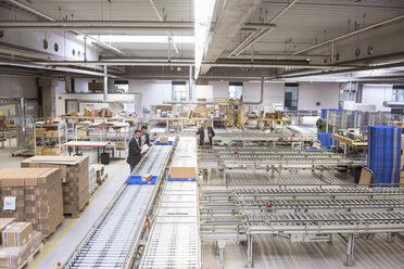 Three businessmen at conveyor belt in factory - DIGF01760