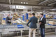 Three businessmen at conveyor belt in factory - DIGF01763