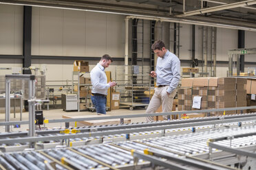 Two men at conveyor belt in factory looking at cell phones - DIGF01766
