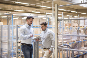 Two men in factory warehouse looking at tablet - DIGF01775