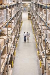 Two men walking in factory warehouse - DIGF01778